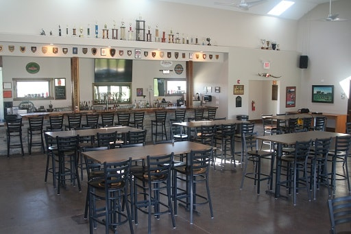 Front view of the bar with tables and chairs, Inside Blaze Clubhouse