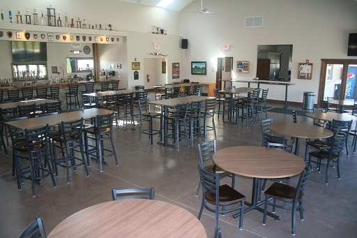 Inside Blaze Clubhouse - Front kitchen counter wide view, tables and chairs